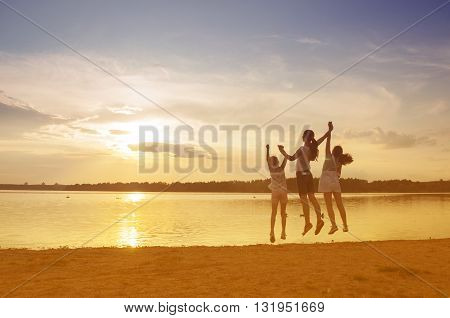family at sunset near the shore of the lake in summer