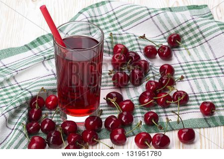 Juice and red cherries on wooden desk