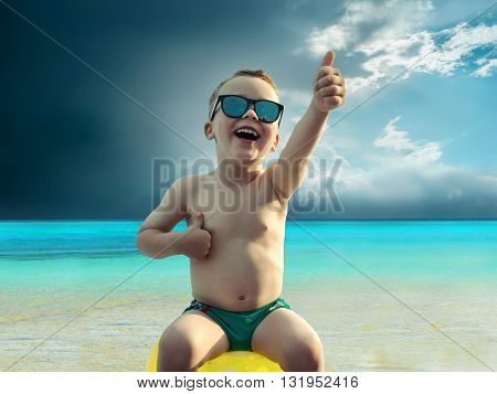 Child in sunglasses fun near the water under sunlight