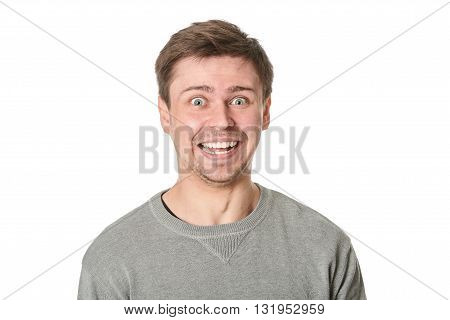 Young man with manic expression on gray background