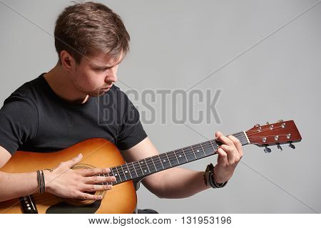 Young man with light beard playing acoustic guitar