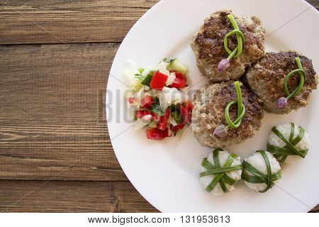 meat patties with balls of rice wrapped in green onion