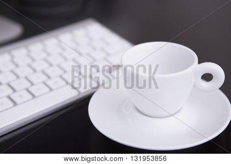 Cup of coffee keyboard on office white table. near office window. empty cup near keyboard.