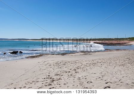 KALBARRI,WA,AUSTRALIA-APRIL 20,2016: Tourists body surfing the turquoise Indian Ocean waves at Jake's Point beach with sandstone rock and coastal dunes under a blue sky in Kalbarri, Western Australia.