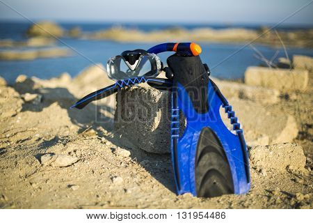 Vacation Start Here Concept Scuba Diving Equipment On The White Sea Sand Beach with Crystal Clear Sea and Sky in Background used as Template.Blue flippers and swimming mask