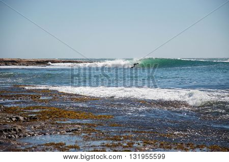 KALBARRI,WA,AUSTRALIA-APRIL 20,2016: Tourist surfing the rocky point break in Indian Ocean waves at Jake's Point with rocky reef and clear blue skies in Kalbarri, Western Australia.