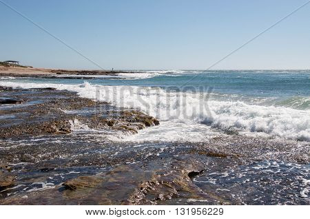 Turquoise seascape with natural rock formations, Indian Ocean  waves, and reef at Jake's Point beach under a clear blue sky in Kalbarri, Western Australia.