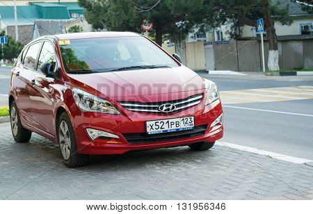 SOCHI, RUSSIA - APRIL 29 2016: A red Hyundai Solaris parked in the streets of Sochi. New korean car.