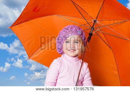 Little cute girl with an orange umbrella isolated on background sky and clouds.