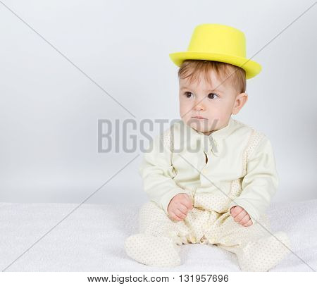Baby In The Yellow Hat Sits .