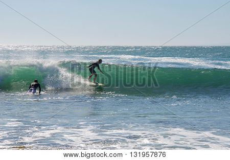 KALBARRI,WA,AUSTRALIA-APRIL 20,2016: Two surfers in the turquoise-green waves of the Indian Ocean at Jake's Point in Kalbarri, Western Australia.