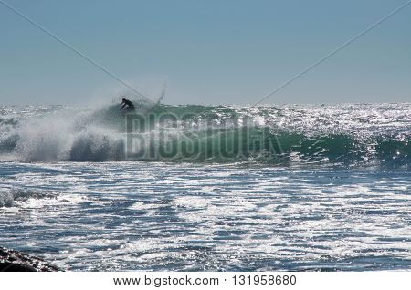 KALBARRI,WA,AUSTRALIA-APRIL 20,2016: Person surfing in the turquoise waves of the Indian Ocean at Jake's Point in Kalbarri, Western Australia.