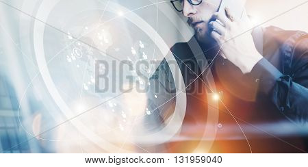 Photo bearded adult hipster working modern urban loft.Man wearing black shirt and speaking contemporary smartphone.Connections world wide interfaces screen.Wide, film effect, flares.Blurred background