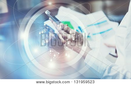 Image business woman wearing white shirt, touching screen modern smartphone.Open space loft office.Report documents, blurred background.Connections world wide interfaces.Horizontal, flares.Film effect