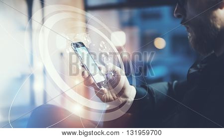 Closeup photo businessman relaxing modern loft office.Man sitting in chair at night.Using contemporary smartphone, blurred background. Digital Connections World Wide Interfaces.Horizontal, film effect