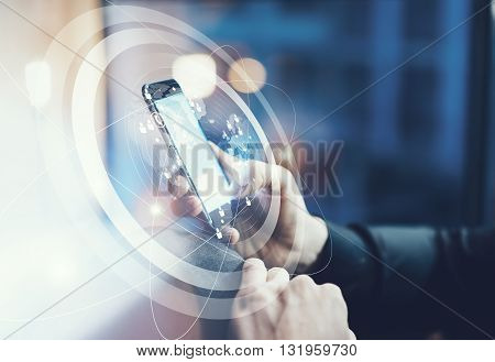 Photo businessman relaxing modern loft office. Man sitting in chair at night.Using contemporary smartphone. Digital Connections World Wide Interfaces Screen. Horizontal, film effect, blurred background