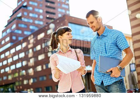 young man, wearing in blue t-shirt and sunglasses and woman with thin, elegant flexible laptop on the green background in the park or business center or univercity area. learning or business concept