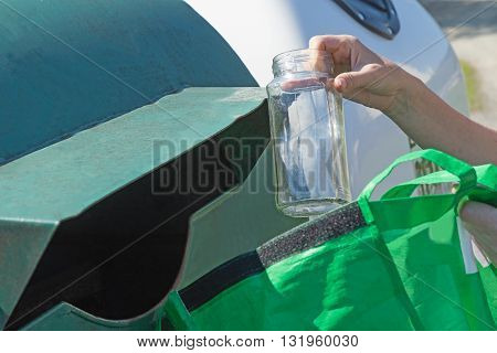 The woman is throwing a glass bottle from green portable bag to green container for sorting glass household waste.