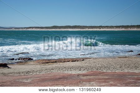 Indian Ocean waves rush the rocky, sandy beach at Jake's Point in Kalbarri, Western Australia on a clear day.