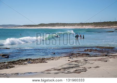 KALBARRI,WA,AUSTRALIA-APRIL 20, 2016: Tourists body surfing in the turquoise Indian Ocean waters at the tourist destination Jake's Point in Kalbarri, Western Australia.