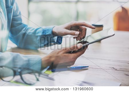 Woman Touching Digital Tablet Hand.Reflections Screen.Project Producer Researching Process.Young Business Crew Working with New Startup Studio. Blurred, film effect. Horizontal closeup photo