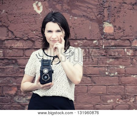Woman photographer with vintage camera in hand on vintage brick wall background. Toned photo with copy space. Vintage style photo.