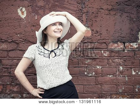 Smiling young woman in a white blouse and a hat posing against vintage brick wall background. Vintage portrait of a woman. Toned photo with copy space. Vintage style photo.