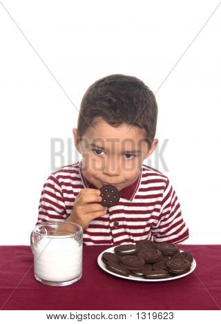 Boy With Chocolate Sandwich Cookies And Milk