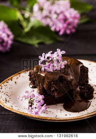 Brownie with black currants, watered with chocolate on a dark wooden background with a bouquet of lilacs