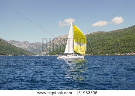Tivat, Montenegro - 26 April, Yacht with white and yellow sail, 26 April, 2016. Regatta