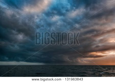 A dramatic rain formation in the distant Pacific Ocean pours rain in a small section of cloud cover