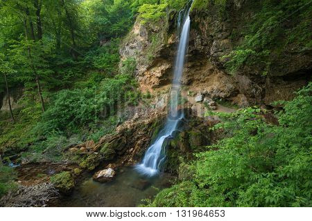 Waterfall surrounded with green trees. This handmade waterfall is situated in Lillafured park (Hungary).