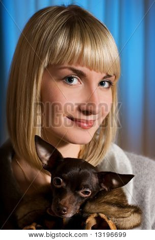 Elegant girl with funny little dog in luxury dog's clothing