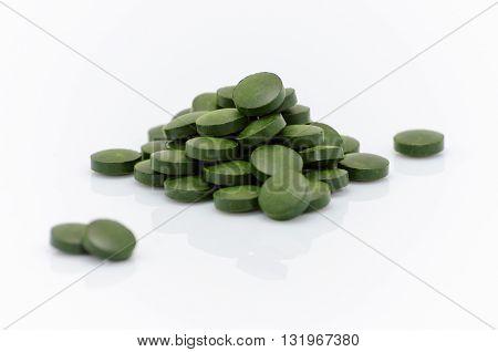 spirulina chlorella seaweed pills close up on white