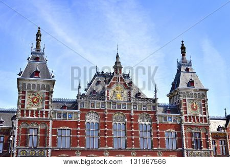 Amsterdam Centraal Station. Building exterior of Amsterdam Centraal and blue sky with flying seagull. Capital city of the Netherlands, central station or metro station.