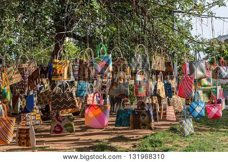 A street market in Maputo Mozambique where hand crafted bags are displayed by hanging them on a tree