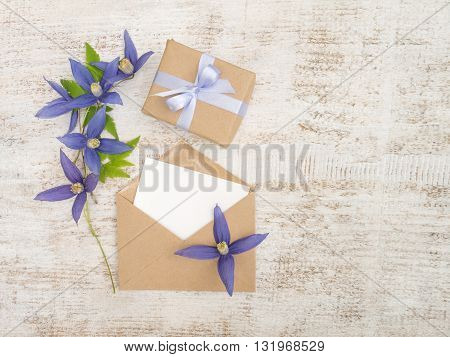 Gift box with violet satin bow blue flowers and envelope with greeting card on the wooden painted board