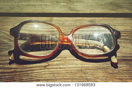 Old broken glasses on a wooden background