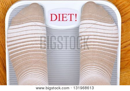 Person standing on the weight scale. The scale shows DIET!