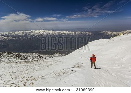 man standing on a snow mountain slope in mountains with snowy picks and blue sky with clouds on background