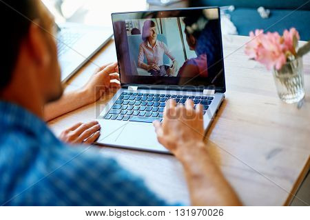 young man and woman with laptop typing on the keyboard in cafe. palm and laptop closeup