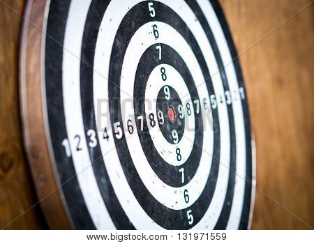 Close-up empty dartboard with numbers, brown wooden background texture