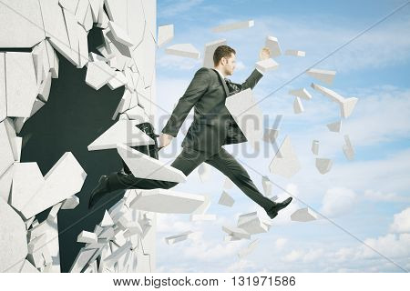 Business breakthrough success concept with businessman jumping through wall on sky background