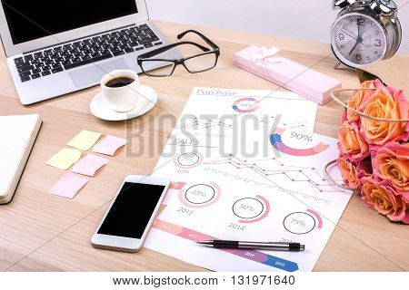 Creative designer desktop with business report blank smart phone screen flowers laptop coffee cup alarm clock and other items. Mock up