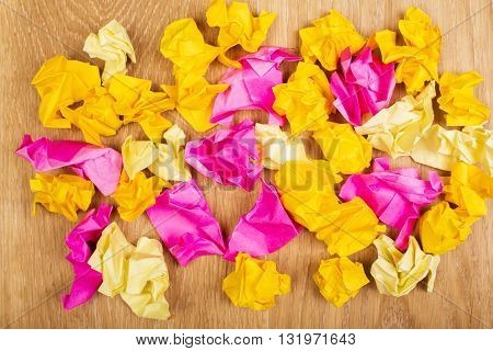 Closeup of colorful crumpled paper on wooden desktop