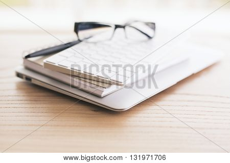 Closeup of spectacles keyboard pen notepads and laptop