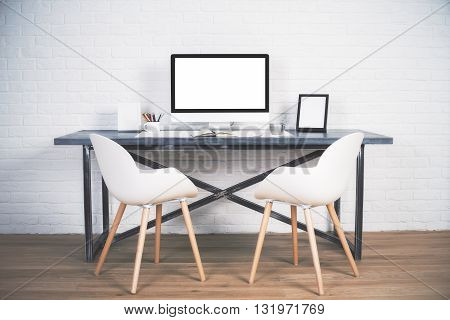 Two chairs next to designer desk with blank white computer screen and other items on wooden floor and brick background. Mock up