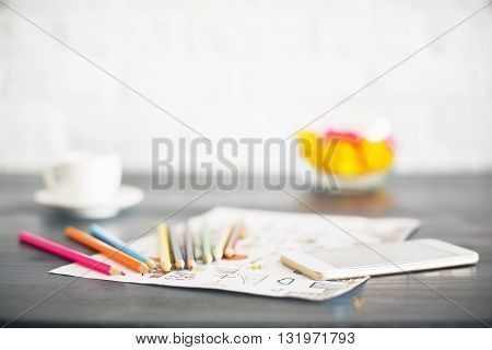 Blurry desktop with colorful pencils sketch smart phone coffee cup and other items