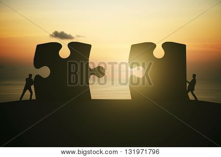 Partnership concept with businesspeople silhouettes putting puzzle pieces together on sunrise background