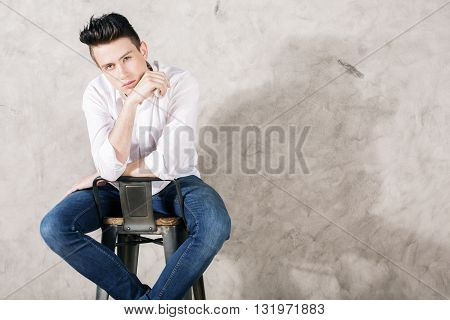Young man in white shirt and jeans sitting backwards on chair against concrete wall